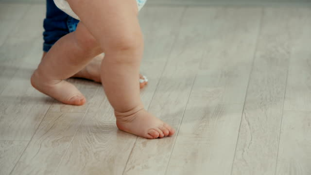 Legs of mother and baby. Baby Daughter Take First Steps видео