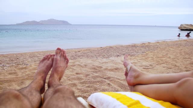 legs of people lying on beach sun lounger near the sea - giuntura umana video stock e b–roll