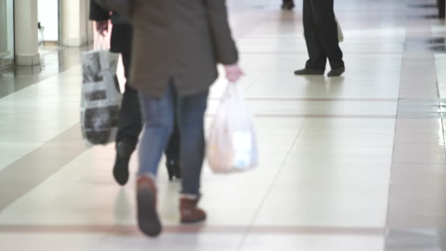 Legs of people walking around the store video