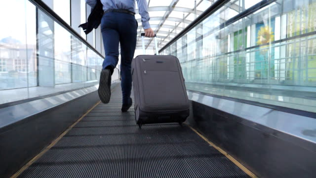 Legs of successful businessman running in hall of terminal and pulling suitcase on wheels. Follow to young man with his luggage is late for flight. Guy hurry to business trip. Slow motion Legs of successful businessman running in hall of terminal and pulling suitcase on wheels. Follow to young man with his luggage is late for flight. Guy hurry to business trip. Slow motion human foot stock videos & royalty-free footage
