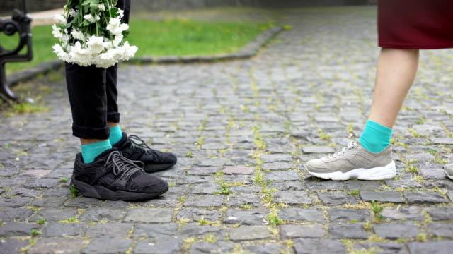 ben av tonåringar, flickvän kommer till pojkvän med blommor, stående på tiptoes - på tå bildbanksvideor och videomaterial från bakom kulisserna