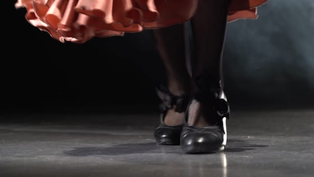 Legs of the girl are tap dancing. Light from behind. Smoke background. Close up