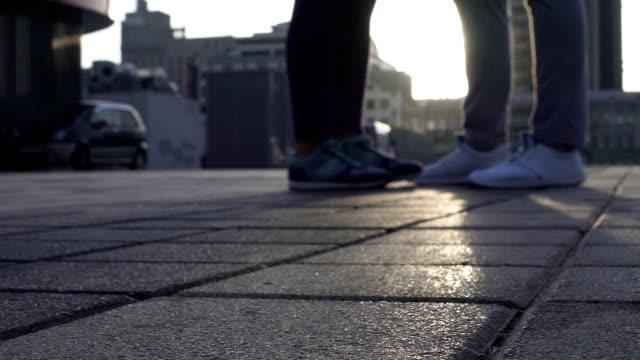 ben av två älskande kyssas i tomma city square, romantisk relation, känslor - på tå bildbanksvideor och videomaterial från bakom kulisserna