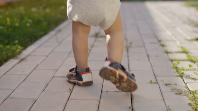Legs of Unrecognizable Toddler Walking on Footpath Outdoors