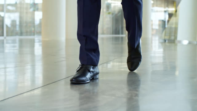 Legs of Walking Businessman Closeup low angle shot of legs of unrecognizable businessman walking through large office center shoe stock videos & royalty-free footage
