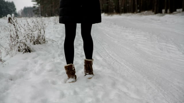 Legs of woman walking on snow with footprints on snowy day video