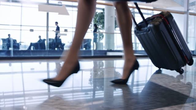 vídeos de stock, filmes e b-roll de pernas de mulher de salto alto andando no aeroporto com a bagagem com rodas - salto alto