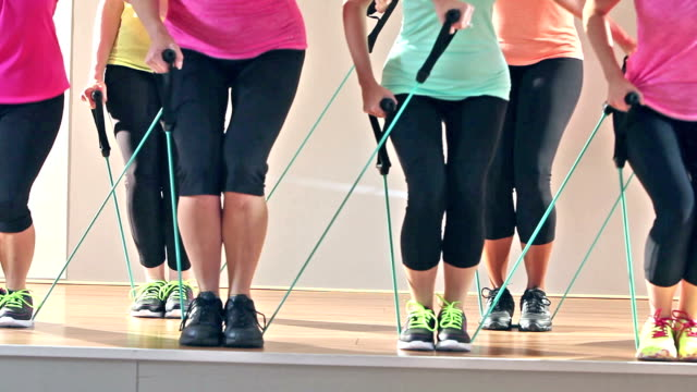 legs of women in exercise class using resistance bands - inarcare la schiena video stock e b–roll