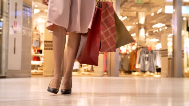 legs of young girl goes shopping in mall, holds bags, shopping concept, fashion concept - borsa della spesa video stock e b–roll