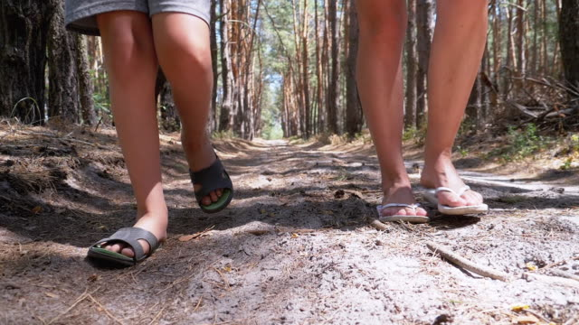Legs of Young Mother and Son Walking Along Path in Forest in Summer. Slow Motion