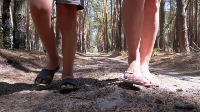 legs of young mother and son walking along path in forest in summer. slow motion - pantaloncini video stock e b–roll