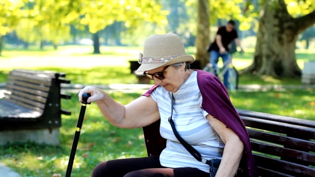 Legs pain Senior Woman with pain in legs difficult to get up from the park bench. People in the background. aging process stock videos & royalty-free footage