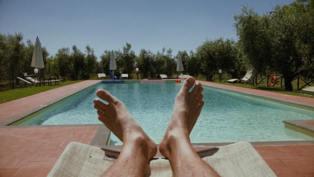 legs relaxing point of view: in a swimming pool - загар стоковые видео и кадры b-roll