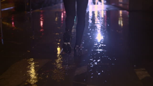 SLO MO TS Legs running in the city on rainy night Slow motion medium rear view  surface level tracking shot of  female legs in jogging motion on a rainy night in the city. drenched stock videos & royalty-free footage