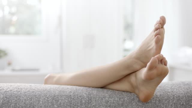 vídeos de stock e filmes b-roll de legs up on back side of the sofa - sofá