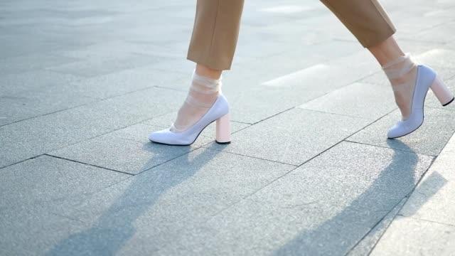 gambe camminare piedi femminili scarpe bianche nylon alla moda - scarpe video stock e b–roll