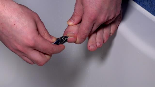 vídeos de stock, filmes e b-roll de pernas com unhas compridas e homem mão de ferramentas de corte para pedicure - pedicure