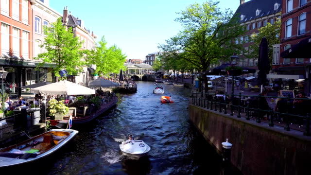 Leiden canals in Netherlands canals in old town with historical houses of Leiden, Netherlands dutch architecture stock videos & royalty-free footage