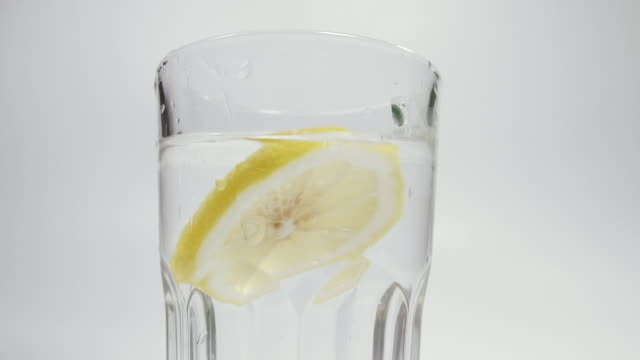 lemon. a lemon falls into a glass of water. shot in slow motion - decanter video stock e b–roll