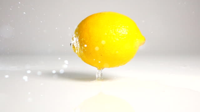 Lemon fall down on white surface video