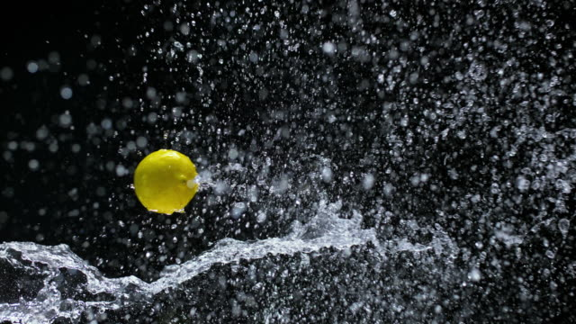 SLO MO Lemon flying through water splash in the air video
