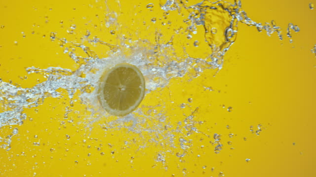 SLO MO Lemon half colliding with water on yellow background video