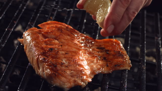 lemon is squeezed on salmon - grilling stock videos & royalty-free footage