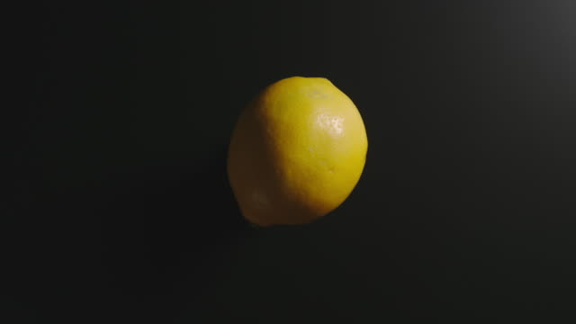 Lemon rotates on a black surface. Top view. Stop motion video