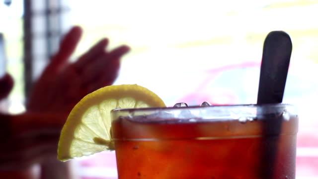 Lemon sitting ontop of glass of Iced Tea in restaurant