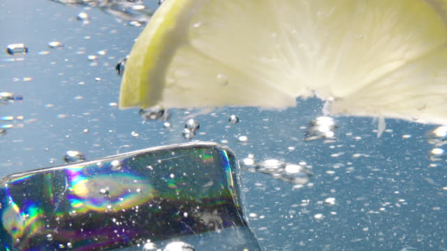Lemon slice and ice cube falling down in water Lemon slice and ice cube falling down in water tonic water stock videos & royalty-free footage