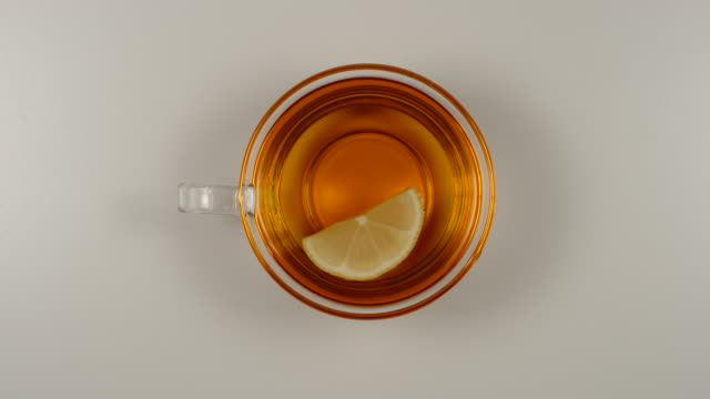 top view: lemon slice rotates in a black tea in a glass tea cup - tea cup stock videos & royalty-free footage