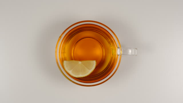 top view: lemon slice swims in a black tea in a glass tea cup on a table - tea cup stock videos & royalty-free footage
