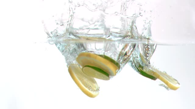 Lemon slices falling into water in super slow motion video