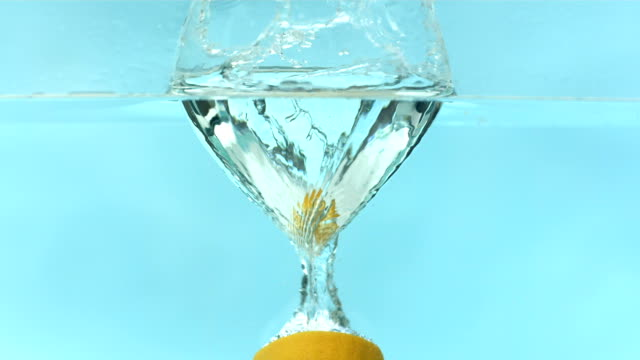 Lemon splashing into water, slow motion video