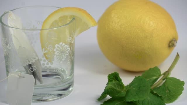 lemon tea in a still life with teapot and glass - лимонный сок стоковые видео и кадры b-roll