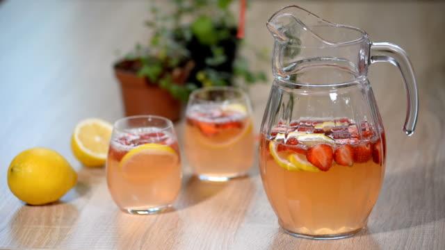 vídeos de stock e filmes b-roll de lemonade with fresh srtawberries, lemons and ice. - limonada tradicional