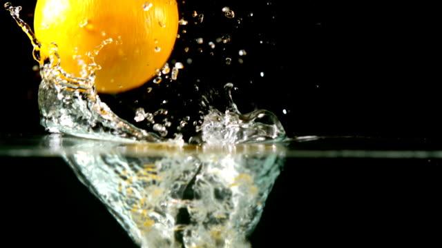 Lemons falling in water on black background video