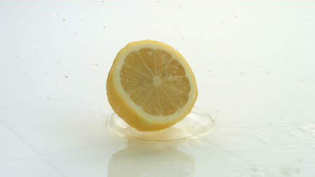 Lemons splashing into water, slow motion video