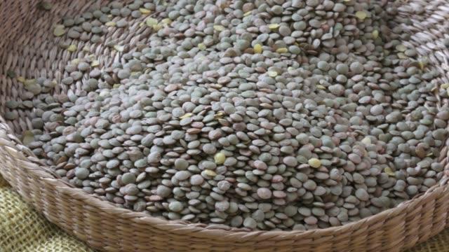 レンズの culinaris はレンズ豆マメ科の学名です。籐のバスケットは、穀物に。マメ豆菜食主義の食糧のため。 - 木目点の映像素材/bロール