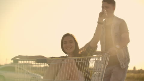 bagliore dell'obiettivo: persone allegre coppia uomo e donna al tramonto cavalcano i carrelli dei supermercati al rallentatore - concetti e temi video stock e b–roll