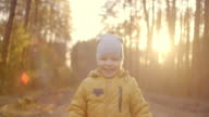 istock Lens Flare in Slow Motion: Happy baby boy running in autumnal park. Little child playing on autumn walk. Autumnal forest with golden leaves. Autumnal forest with golden leaves 1221390127