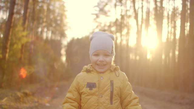vídeos de stock e filmes b-roll de lens flare in slow motion: happy baby boy running in autumnal park. little child playing on autumn walk. autumnal forest with golden leaves. autumnal forest with golden leaves - criança pequena