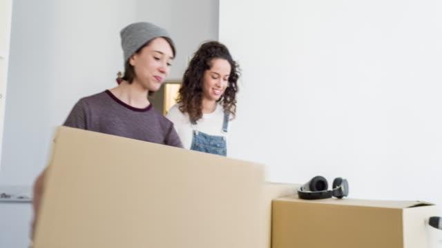lesbisk par bära kartong lådor i nya hem - flyttlådor bildbanksvideor och videomaterial från bakom kulisserna