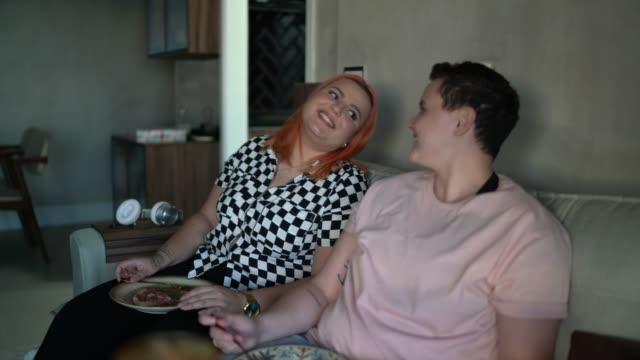 自宅でソファでピザを食べるレズビアンのカップル - オルタナティブカルチャー点の映像素材/bロール