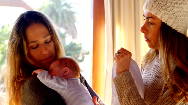 Lesbian couple holding their baby boy in living room 4k Lesbian couple holding their baby boy in living room at home 4k lesbian stock videos & royalty-free footage