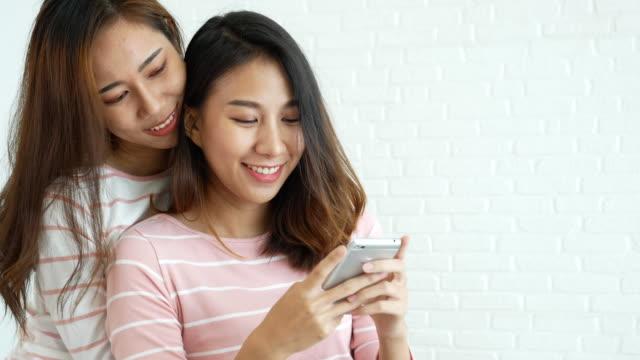 vídeos de stock, filmes e b-roll de estilo de vida homossexual da felicidade dos pares lesbian na cama. duas linda namorada falar, abraçar e rir juntos relação se apaixonar. conceito de estilo de vida lgbtq relation. - mobile