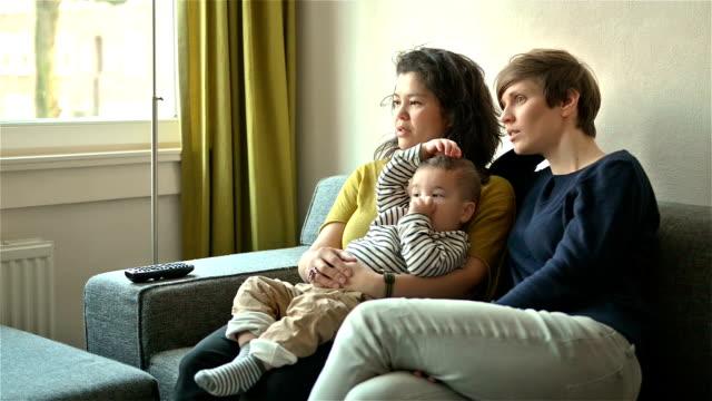vídeos de stock, filmes e b-roll de lésbica casal assistindo tv com seu filho - pais
