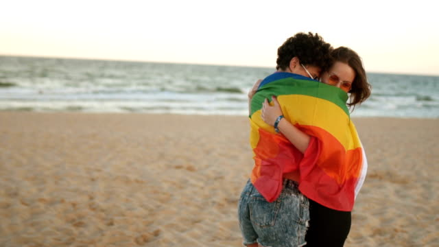 Lesbian couple with rainbow flag Lesbian couple standing wrapped in LGBT flag on sandy beach. lgbtqi rights stock videos & royalty-free footage