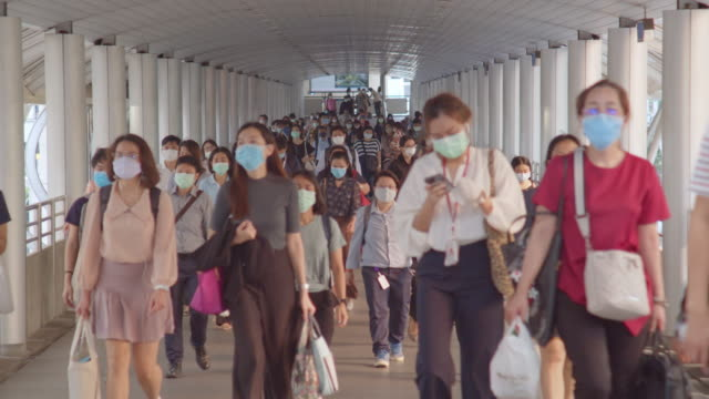 less crowded asian people wear face mask, walk in pedestrian walkway. coronavirus disease covid-19 pandemic outbreak effect, social distancing city life or pm 2.5 air pollution concept. 4k slow motion - tajowie filmów i materiałów b-roll