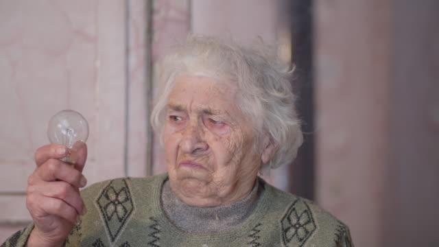 lassen sie es led sein. glühbirne evolution. close-up portrait einer aktiven seniorin, die ihre wahl für die zukunft trifft. echte menschen leben. - led leuchtmittel stock-videos und b-roll-filmmaterial